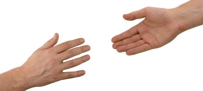 Handen reiken naar elkaar.